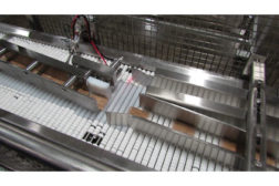 An automated diverter feeds bars to each of the line's shrink wrappers on conveyors