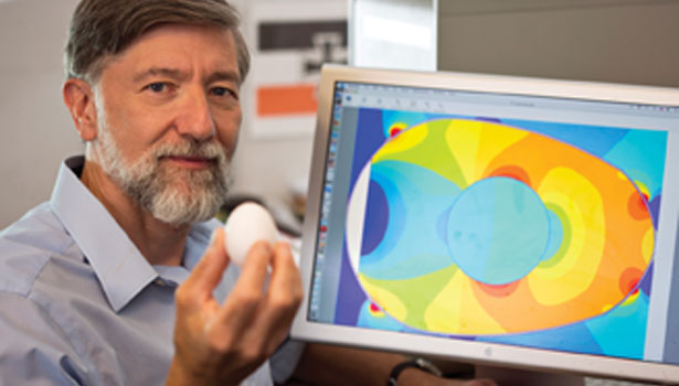 PPPL Engineer Chris Brunkhorst displays an egg while a computer image simulates the levels of RF power that different parts of an egg absorbed during an experiment.
