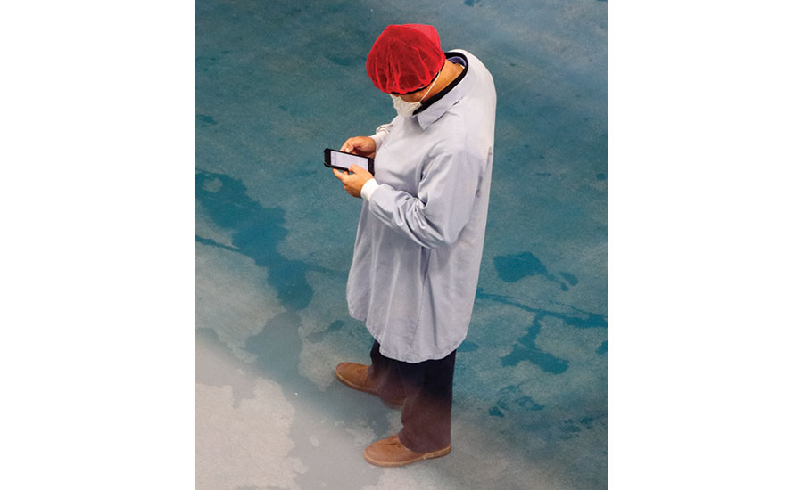 Worker using smartphone to check process status